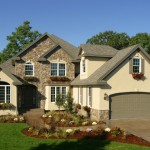 Newly constructed home exterior with beautiful stone and landscaping.